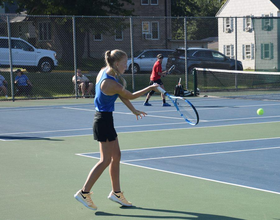 Megan Johnson returns a ball during her tennis match