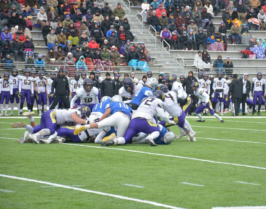 The Owatonna offensive line pushes the pile forward on a quarter back sneak