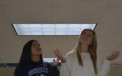 Juniors Liv Larson and Asia Buryska looking up at the PA Speaker