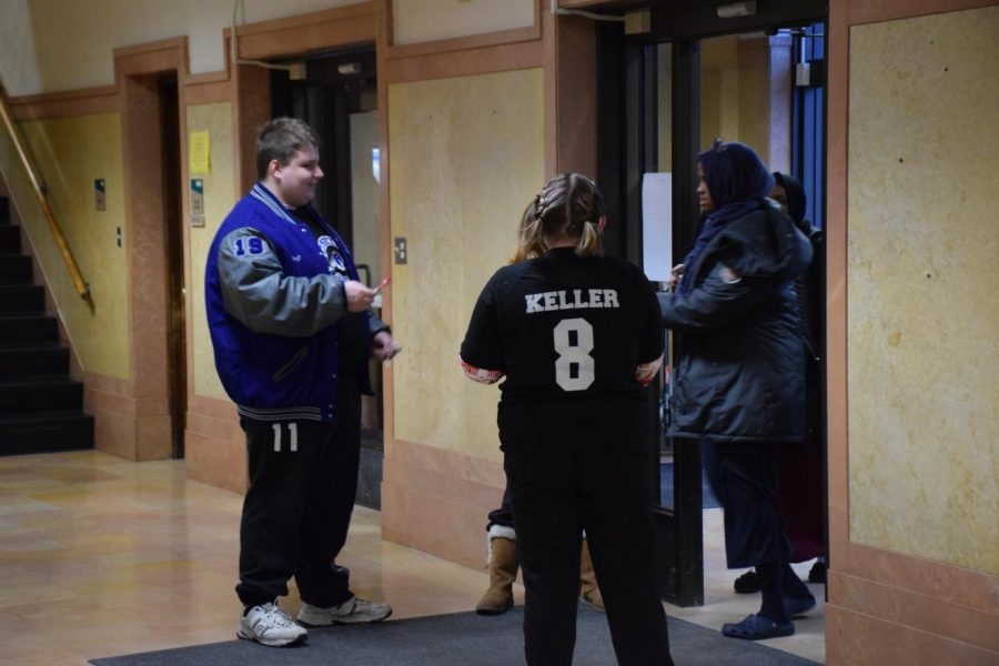 Adaptive floor hockey players hand out candy as students walk into school