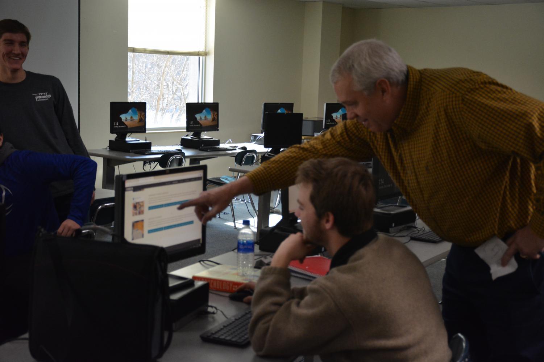 DECA adviser Mr. Scott Pierce helps out senior Dawson Ringhofer in DECA prep class
