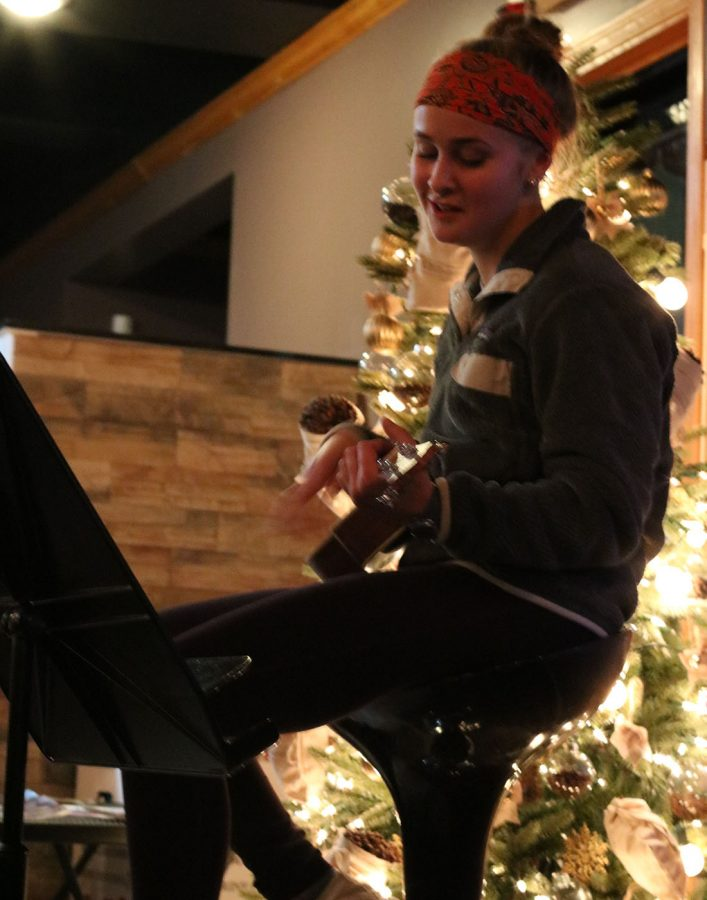 Molly Hawkins plays the ukulele and sings along at the Art Splash