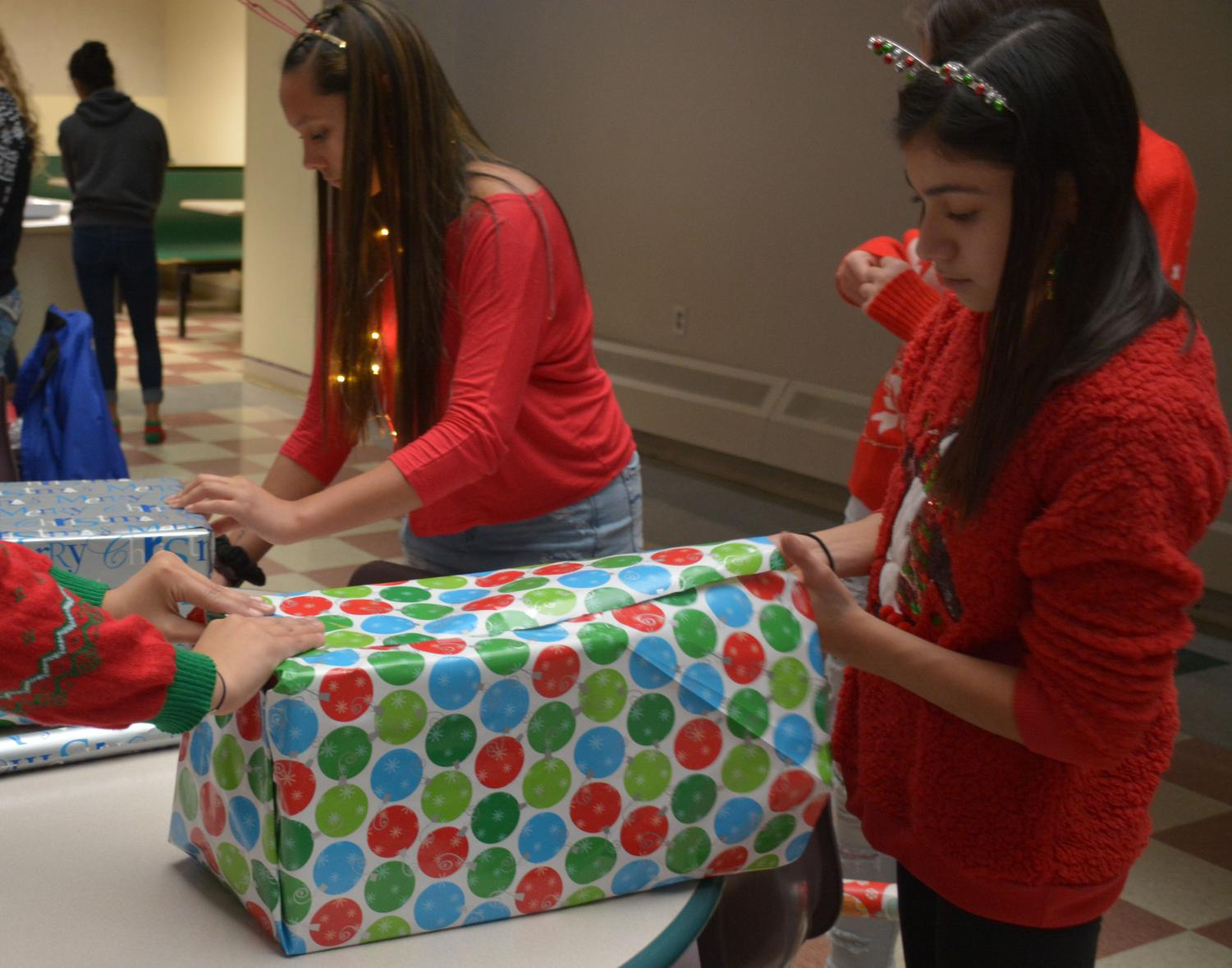 Cheerleaders wrap presents for Big Brothers Big Sisters