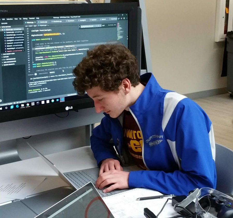 Junior Miles Kuhn programming during robotics.
