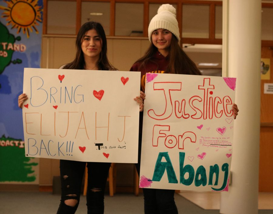 Students with posters asking for classmates to be allowed back at school