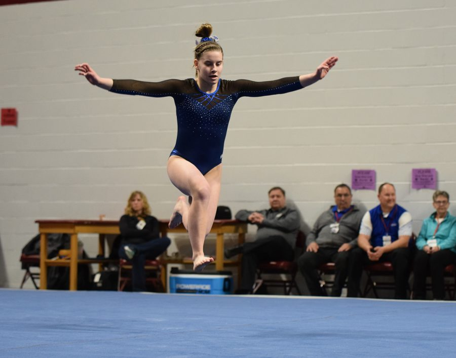 Sophomore Lucy Macius leaps during her floor routine
