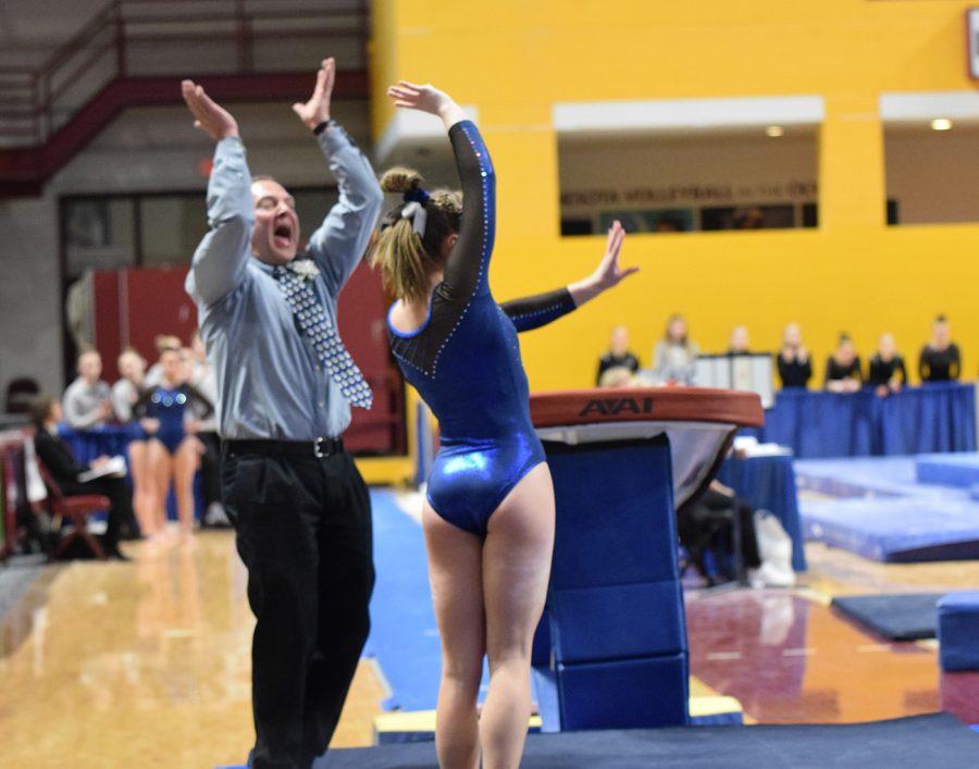 Coach Tom Smith celebrates after sophomore Lindsay Bangs sticks her vault