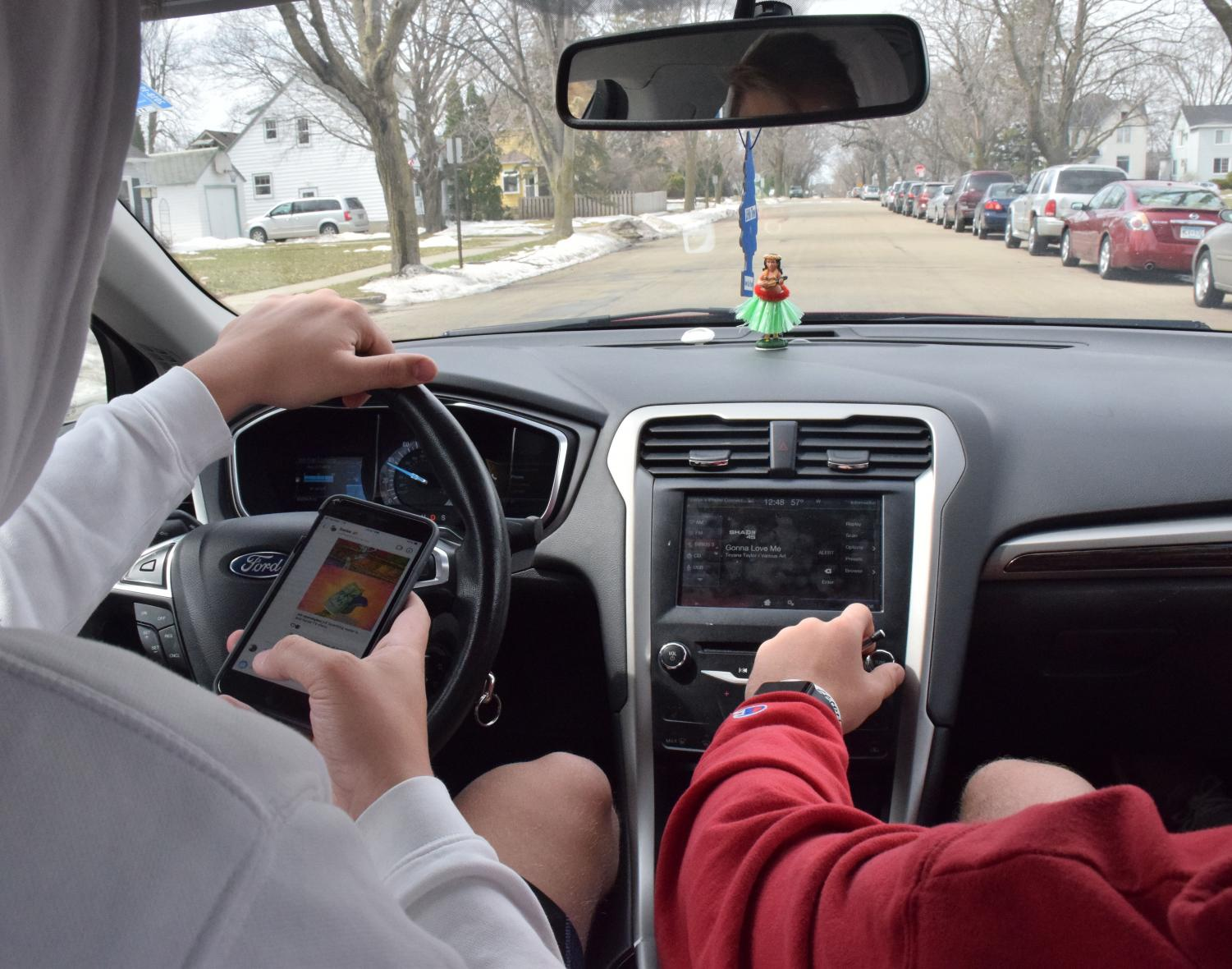 April is Distracted Driving Awareness Month.  Carter Debus simulates being on his phone and driving