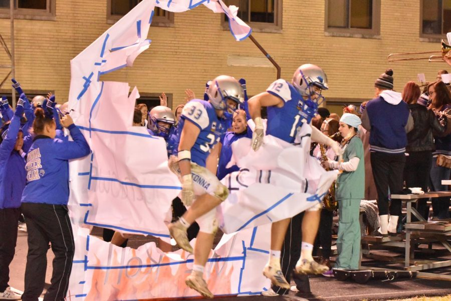 Football team breaking through the poster after halftime