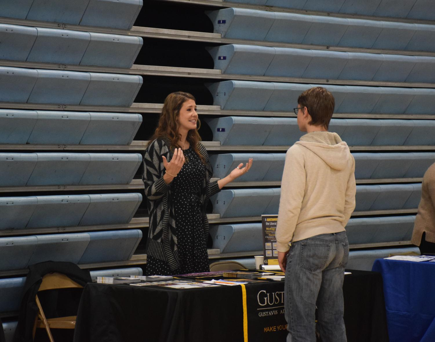 A representative from Gustavus talks with a student