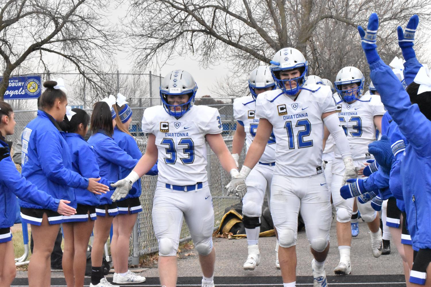 Captains Isaac Gefre, Carson Dekam, and Zach Wiese walk out at halftime of the State Quaterfinals