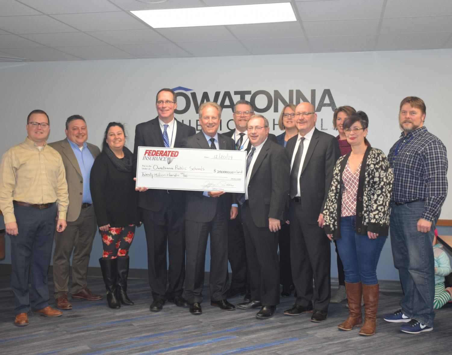 CEO Jeff Fetters and CFO Mike Keller present the check from Federated Insurance to the Owatonna School Board at 7 a.m. on Dec. 20, 2019