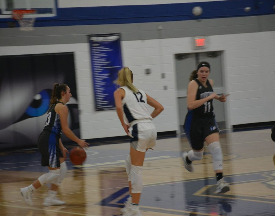 Senior Sara Anderson(left) and sophomore Lexi Mendenhall(right) running up the court
