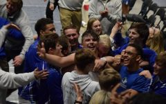 Owatonna Wrestling surrounds Isaiah Noeldner after his pin to send the team to the state tournament