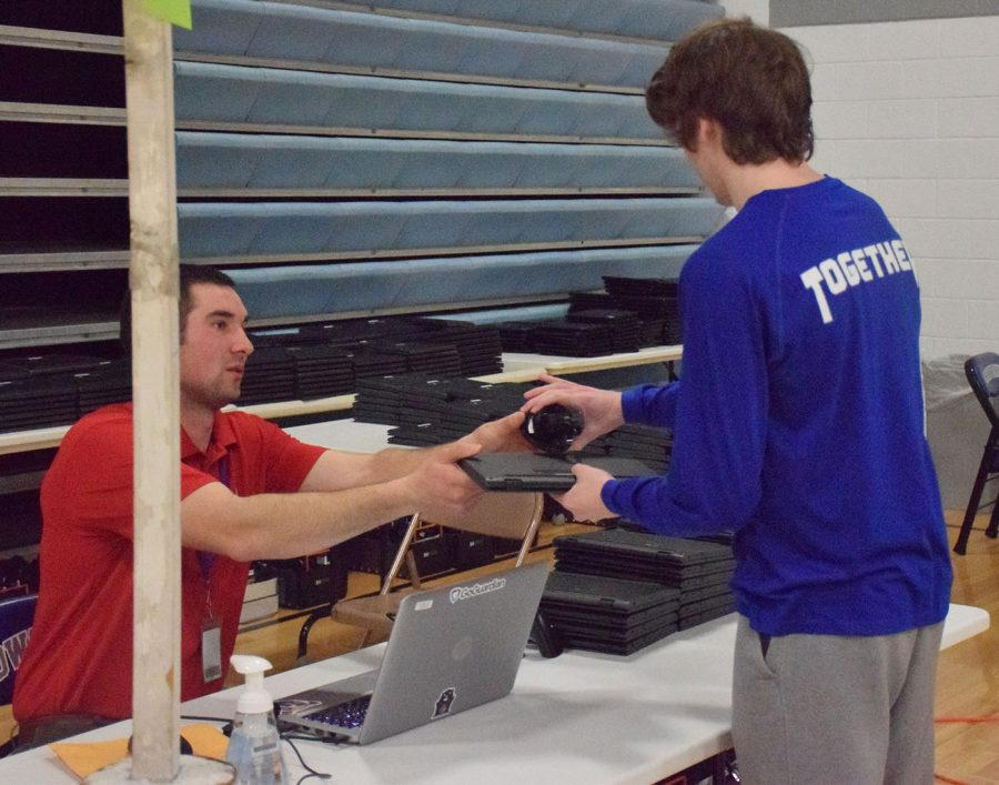 IT specialist, Ben Schmidt, hands a computer and charger to senior Aidan Cords
