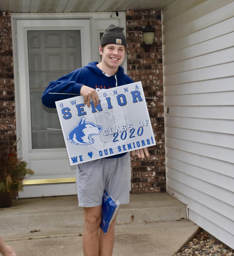 Senior Carter DeBus excited about receiving his cap, gown and yard sign