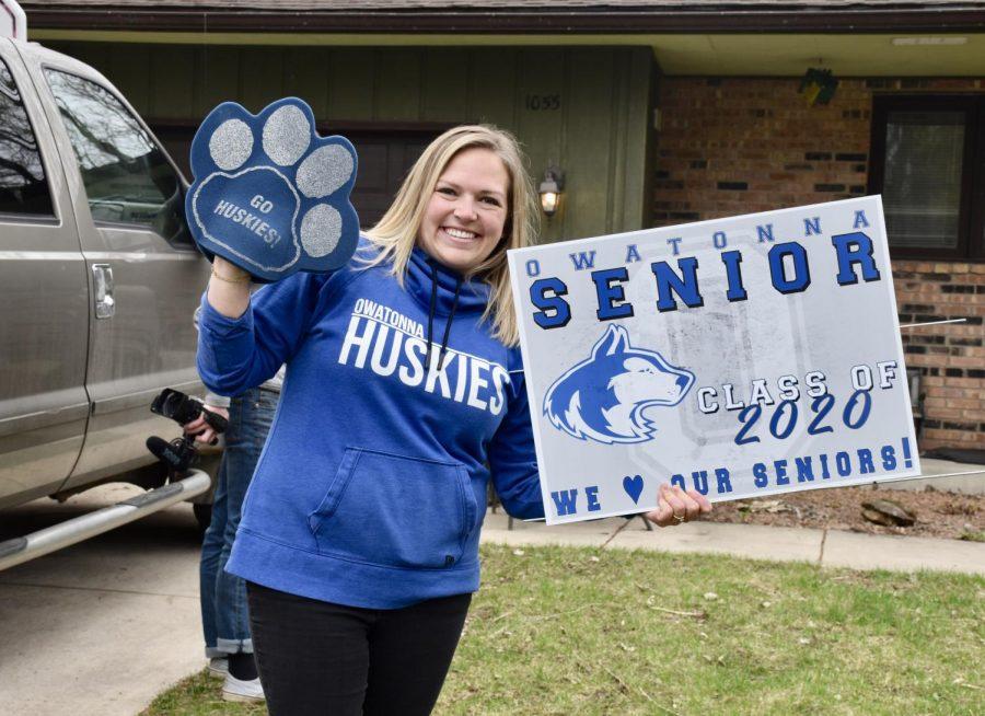Mrs. Gendron holding up the yard sign that seniors recieved