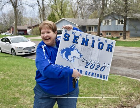 Ms. Lage holding up the senior yard sign