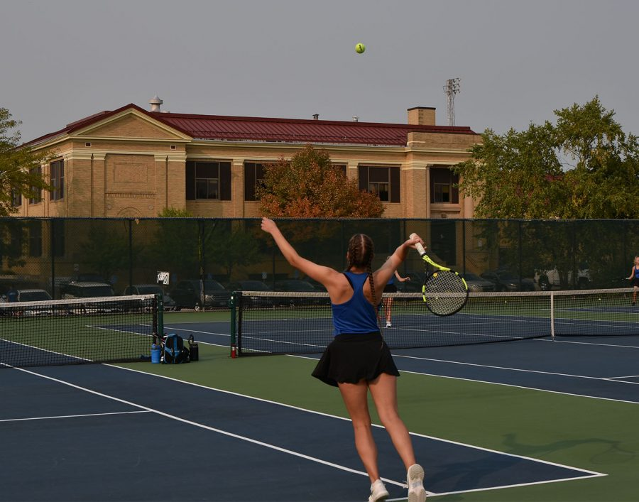 Cora Barrett stretches to hit her serve to the other #1 doubles team