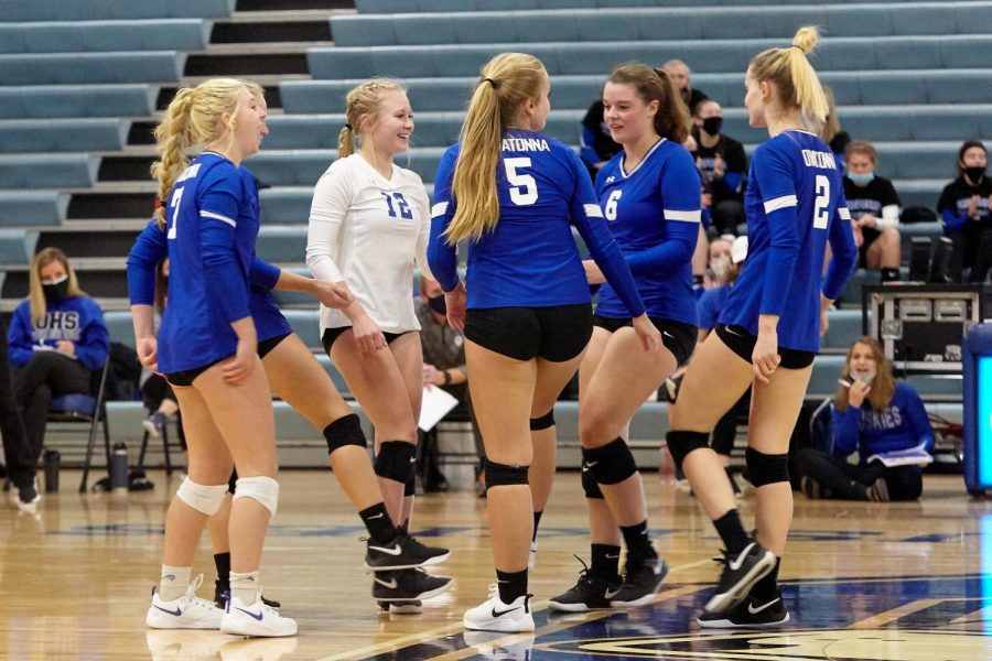Huskies girls volleyball players celebrate and converse after a gained point