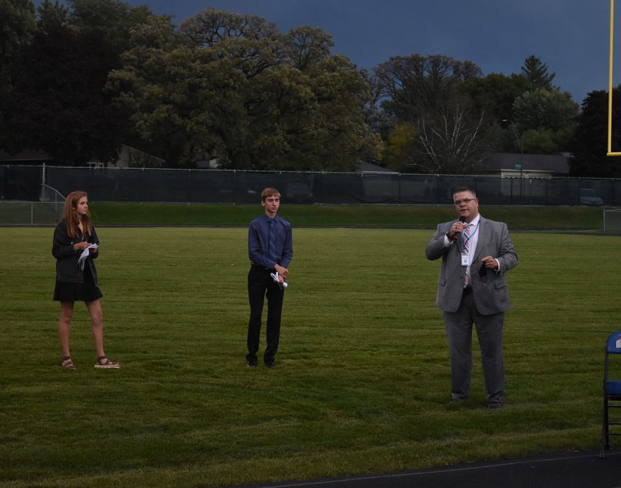 Mr. Elstad giving a speech before naming homecoming king and queen