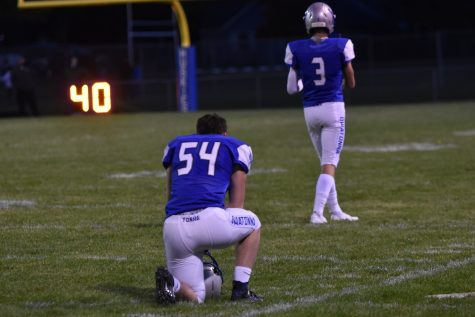 Senior Abe Stockwell takes a knee to pray before the game begins.