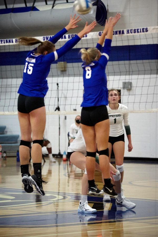 Jenna Gleason (15) and Abby Smith (8) go up for a block.