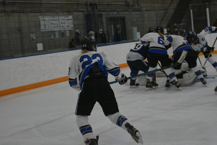 Ezra Oien watches as many huskies players fight for the goal