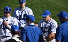 The Owatonna Baseball team meets outside of the dugout after a tough inning in the field.