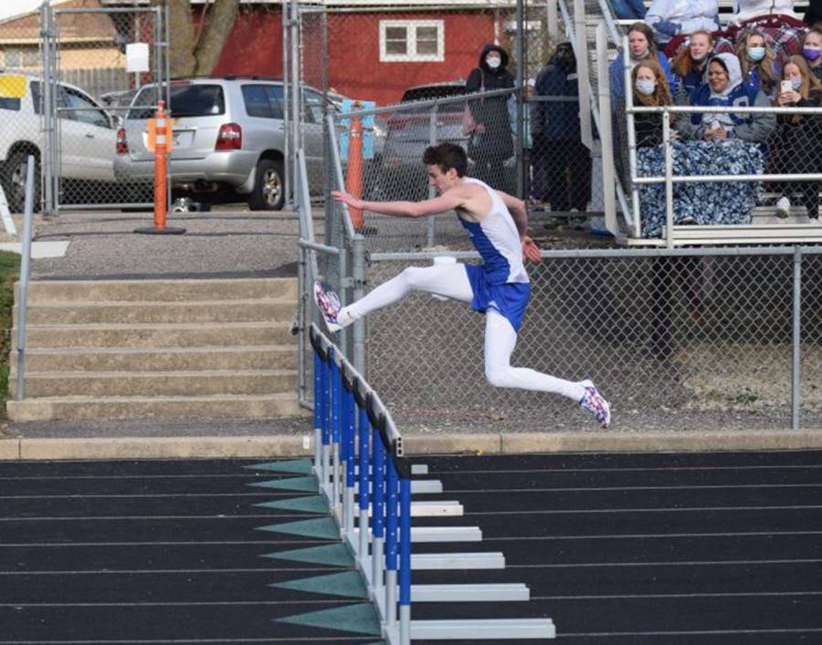 Ryan Gregory jumping over a hurdle