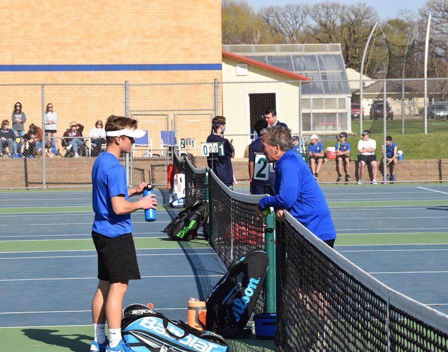 Senior Caleb Schuler talks with head tennis coach Curt Matejcek between matches