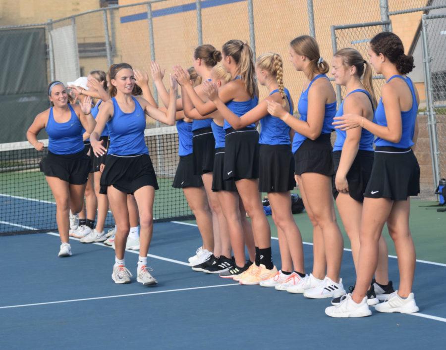 Girls tennis high-five line up.