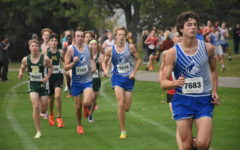 The Huskies varsity runners stride down the course in a pack.