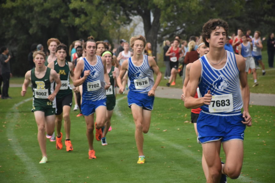 The+Huskies+varsity+runners+stride+down+the+course+in+a+pack.