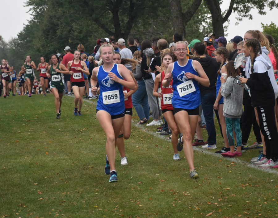 Girls cross country runners pace each other during the home meet